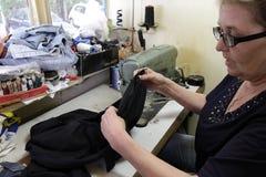 De kleermaker naait kleren in uitstekende workshop in Sofia, Bulgarije - september 9, 2015 De mensen naaien kleren Het herstellen Stock Foto
