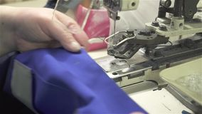 De kleermaker naait knopen aan overall op een speciale machine stock videobeelden