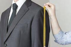 De kleermaker neemt metingen van kostuum, witte geïsoleerde achtergrond, stock fotografie