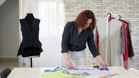 De kleermakersvrouw meet de band van het doekgebruik op lijst om patroon aan toekomstige kleren te maken stock video