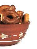 De kleikom, een plaat, een kom, ongezuurde broodjes, pretzels, isoleert, witte achtergrond Stock Afbeeldingen