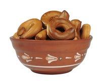 De kleikom, een plaat, een kom, ongezuurde broodjes, pretzels, isoleert, witte achtergrond Stock Fotografie