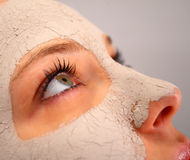 De kleimasker van het kuuroord op het gezicht van een vrouw Stock Foto