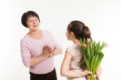De kleindochter verbergt een boeket van bloemen voor de grootmoeder Royalty-vrije Stock Afbeelding
