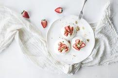 De kleine aardbei en pistachecakes van het pavlovaschuimgebakje met mascarponeroom royalty-vrije stock foto's