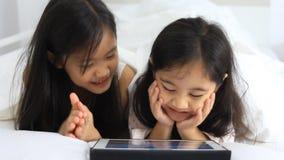 De kleine Aziatische meisjes genieten van met tablet stock videobeelden