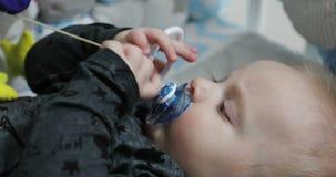 De kleine baby met een fopspeen in zijn mond speelt met een rammelaar stock video