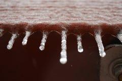 De kleine bevroren ijskegels bengelen van houten paneel stock foto's
