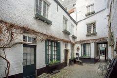 De kleine binnenplaats in oude stijl smalle straat met bakstenen muren en cobbled stenen Royalty-vrije Stock Afbeelding
