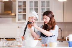 De kleine dochter in de de hoed en schort van de chef-kok en haar moeder bereiden baksel in de heldere, klassieke keuken voor stock foto's