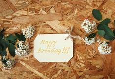 De kleine Gele Kaart van de Wensverjaardag met Witte Bloemen en Groene Bladeren op de Textuur Houten Achtergrond Hoogste mening Royalty-vrije Stock Foto's