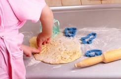 De kleine handen bereiden koekjes in de keuken voor Royalty-vrije Stock Foto's