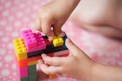 De kleine handen van het kind verzamelt de heldere plastiek gekleurde Ontwerper Onderwijsspeelgoed en vroeg het leren royalty-vrije stock fotografie