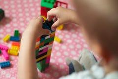 De kleine handen van het kind verzamelt de heldere plastiek gekleurde Ontwerper Onderwijsspeelgoed en vroeg het leren stock fotografie