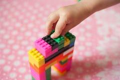 De kleine handen van het kind verzamelt de heldere plastiek gekleurde Ontwerper Onderwijsspeelgoed en vroeg het leren stock foto's
