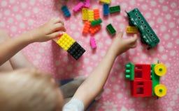 De kleine handen van het kind verzamelt de heldere plastiek gekleurde Ontwerper Onderwijsspeelgoed en vroeg het leren royalty-vrije stock afbeelding