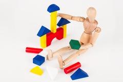 De kleine houten ledenpop zit de bouw kleurrijke blokken die op w worden geïsoleerd Royalty-vrije Stock Foto