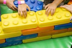 De kleine jonge geitjes bouwt een piramide van grote delen van de ontwerper Multi-colored kinderen` s ontwerper met grote details stock afbeelding