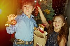 De kleine jonge geitjes verfraaien Kerstboom stock foto