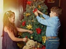 De kleine jonge geitjes verfraaien Kerstboom stock afbeelding