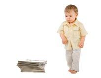 De kleine jongen bekijkt een stapel van boeken Royalty-vrije Stock Afbeeldingen