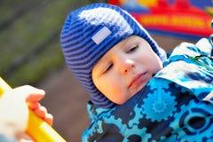 De kleine jongen bij een speelplaats schudt op een schommeling Royalty-vrije Stock Foto