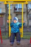 De kleine jongen bij een speelplaats schudt op een schommeling Stock Afbeelding