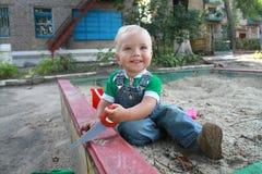 De kleine jongen die in de zandbak spelen Stock Foto's