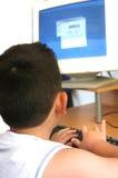De kleine jongen die een computer bestudeert Stock Afbeelding