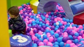 De kleine jongen die op de speelplaats met ballen spelen stock footage