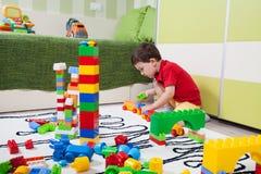De kleine jongen die torens met plastic kubussen bouwen Stock Afbeelding