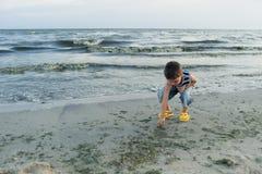 De kleine jongen door het overzees werpt stenen in water Zonsondergang Gelukkige kinderjaren stock foto