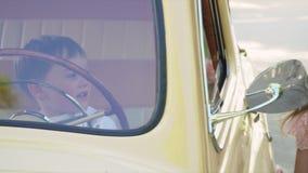 De kleine jongen drijft de grote retro auto, omhoog verliest stock footage