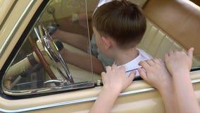 De kleine jongen drijft de grote retro auto, zijn broers en zustersspel in salon stock video