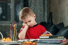 De kleine jongen is droevig, bored om thuiswerk te doen royalty-vrije stock afbeelding