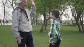 De kleine jongen in een geruit overhemd en het positieve oude mens eindigen om voetbal in het park te spelen De kleinzoon en stock videobeelden