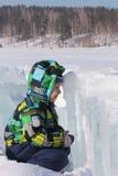 De kleine jongen in een zitting van het kleurenjasje tegengesteld aan aan een ijsblok royalty-vrije stock afbeelding