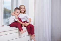 De kleine jongen en meisje die alleen thuis op in het venster het letten royalty-vrije stock fotografie