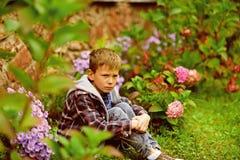 De kleine jongen gaat zitten onder belediging De kleine jongen voelt diep beledigd Kindmisbruik en verwaarlozing Belediging door  royalty-vrije stock afbeeldingen