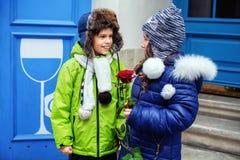 De kleine jongen gaf het meisje toenam Het concept liefde en Valen Stock Foto's
