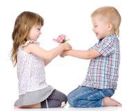 De kleine jongen geeft aan het meisje een bloem Op wit royalty-vrije stock afbeeldingen