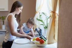 De kleine jongen helpt mamma in de keuken royalty-vrije stock afbeelding