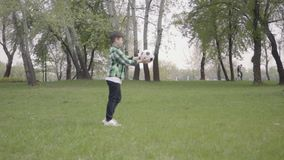 De kleine jongen in het geruite voetbal van de overhemds speelvoetbal in het park Het kind die de bal met zijn voet raken en het stock footage