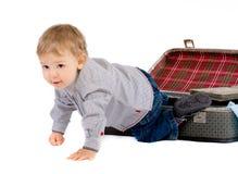 De kleine jongen krijgt uit een koffer Stock Foto's