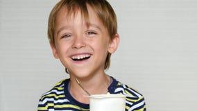 De kleine jongen lacht bij de camera Het kind zit bij de lijst en eet yoghurt Gelukkige emoties Ruwe macaroni op witte achtergron stock footage
