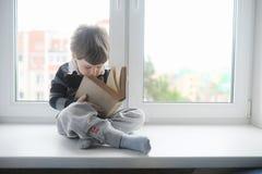 De kleine jongen leest een boek Het kind zit bij het venster a Stock Foto's