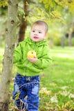 De kleine jongen loopt op een groene open plek met een appel royalty-vrije stock afbeelding