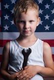 De kleine jongen met de Amerikaanse vlag op de achtergrond, Stock Foto