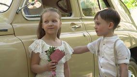 De kleine jongen met de zuster stelt over de grote beige retro auto stock video