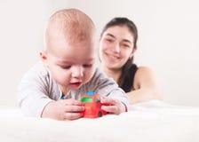 De kleine jongen met een stuk speelgoed en moeder op achtergrond Royalty-vrije Stock Foto